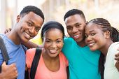 group of cheerful african college friends hugging