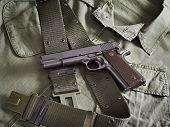 Gun Pistol And Belt Lie On Military Jacket