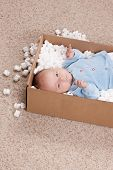 picture of baby delivery  - Newborn baby in open post box with filler on carpet - JPG