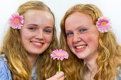 Two sisters with pink flowers in long hair