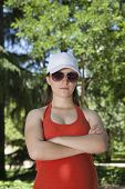 image of sulky  - portrait of young pregnant woman with red shirt threatening face and green trees background - JPG
