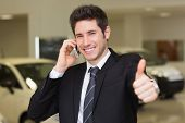 Smiling businessman giving thumbs up on phone at new car showroom