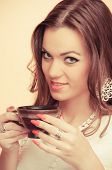 Beautiful young brunette holding cup of coffee, on beige background