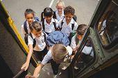 Cute schoolchildren getting on school bus outside the elementary school