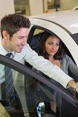 Businessman showing something to his customer at new car showroom