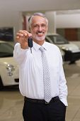 Salesman standing while offering car keys at new car showroom