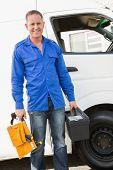 Handyman smiling at camera holding toolbox by his van