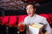 Surprised young man watching a film at the cinema