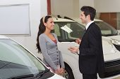 Smiling businessman speaking with his customer at new car showroom