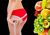 picture of body fat  - Beautiful young woman measuring her body with tape and tropical fruits near her isolated on black - JPG