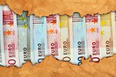 stock photo of paper craft  - Euro banknotes in torn craft paper frame - JPG