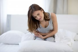 stock photo of hurt  - Young woman sitting on the bed with pain - JPG