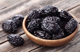foto of prunes  - Prunes on a wooden background - JPG