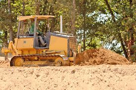 picture of bulldozers  - Small bulldozer moving dirt from a hillside in preperation for a new commerical construction development - JPG