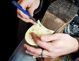 stock photo of draft  - Young shoemaker making a new drafts for new pair of shoes heel - JPG