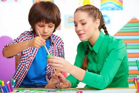 stock photo of cognitive  - Little boy studying with young teacher in a preschool center for children. Teacher helping boy to draw some picture with paint ** Note: Shallow depth of field - JPG