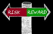 foto of risk  - Opposite arrows with Risk versus Reward. Hand drawing with chalk on blackboard. Choice conceptual image - JPG