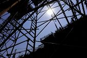 picture of scaffold  - Industrial shot with construction worker silhouetted against blue sky working on a scaffold - JPG