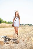 pic of tallgrass  - Hippie looking girl approaching a tree stump - JPG