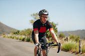 pic of triathlon  - Man triathlon athlete cyclist riding down hill on country road - JPG