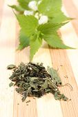 picture of sting  - Heap of dried nettle and fresh stinging nettle with white flowers in background lying on wooden cutting board - JPG
