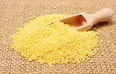 foto of millet  - Heap of yellow millet groats and wooden spoon lying on jute canvas healthy food and healthy nutrition - JPG