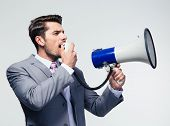 stock photo of shout  - Businessman shouting in megaphone over gray background - JPG