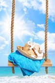 stock photo of anchor  - Summer swing with beach towel and anchor against an ocean blur background - JPG