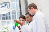 pic of beaker  - Scientists analyzing beakers with chemical fluid in laboratory - JPG