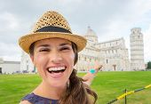 stock photo of piazza  - A smiling female tourist is pointing behind her to the Piazza dei Miracoli and the Leaning Tower of Pisa - JPG