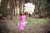 stock photo of swing  - Young woman in pink retro dress is swinging on a swing in summer pine forest - JPG
