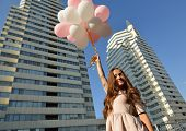 foto of high-rise  - Beautiful young girl holding colored balloons over high - JPG