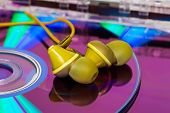 stock photo of analogy  - Yellow earbugs on CD - JPG