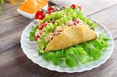 stock photo of tacos  - Tasty taco with vegetables on plate on table close up - JPG