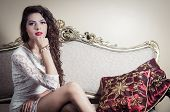 stock photo of bolivar  - Pretty model girl wearing white dress sitting on victorian sofa looking to camera - JPG