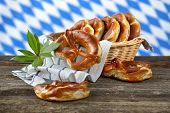 foto of pretzels  - Fresh Bavarian pretzels in a breadbasket on a wooden table - JPG