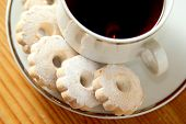 stock photo of sprinkling  - Italian butter biscuits on a saucer of a cup of black tea - JPG