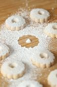 picture of sprinkling  - Italian canestrelli cookie sprinkled with powdered sugar on a wooden table - JPG