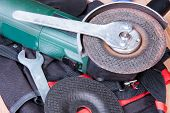stock photo of friction  - Replacement of the grinding wheel of electric grinder with a help of keys - JPG