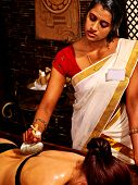 stock photo of panchakarma  - Woman having Indian massage with pouch of rice - JPG