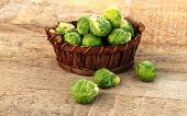 picture of brussels sprouts  - Basket of fresh green brussels sprouts on wooden background - JPG