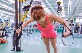 image of suspension  - Portrait of beautiful woman doing hard suspension training with fitness straps in a fitness center - JPG
