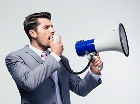 image of shout  - Businessman shouting in megaphone over gray background - JPG