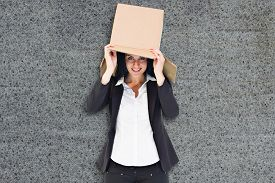 picture of lifting-off  - Businesswoman lifting box off head against grey background - JPG