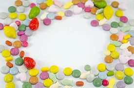 picture of bonbon  - Colorful bonbons arranged in a circle with copyspace left in the center - JPG