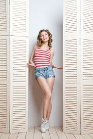 stock photo of jalousie  - Young beautiful woman wearing shorts and  stripy top posing in front of a jalousie - JPG