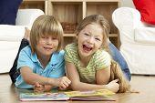 Twee jonge kinderen thuis lezen van boek