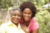 stock photo of grown up  - Senior Woman Hugging Adult Daughter - JPG