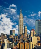 stock photo of empire state building  - Empire State Building and Midtown Manhattan against blue sky - JPG