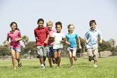 stock photo of gang  - Group Of Children Running In Park - JPG